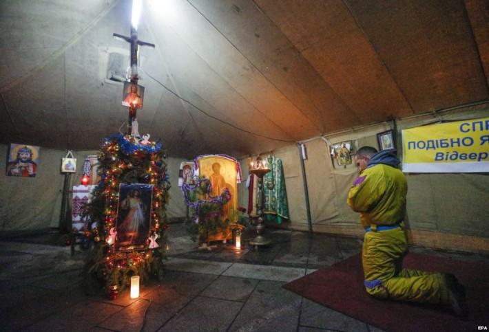 Протестувальник молиться у міжконфесійному молитовному наметі на Майдані незалежності у Києві