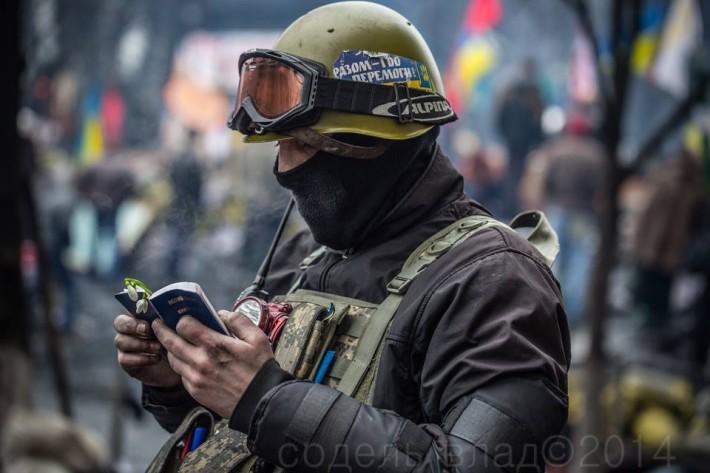 Протестувальник читає Євангеліє на барикадах