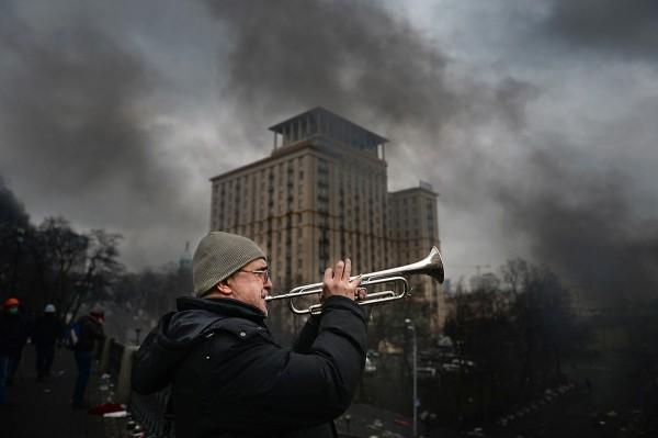 Протестувальник підтримує бойовий дух самооборони Майдану звуками Гімну України, 20.02.2014